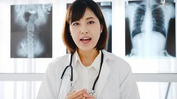jonge Aziatische vrouwelijke arts in wit medisch uniform met stethoscoop met behulp van computerlaptop praten videoconferentiegesprek met patiënt, kijkend naar camera in gezondheidsziekenhuis. advies- en therapieconcept. foto