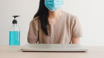 aziatische vrouw die alcoholgel handdesinfecterend middel gebruikt, was de hand voordat ze de laptop opent om het coronavirus te beschermen. vrouw duwt alcohol om schoon te maken voor hygiëne wanneer social distancing thuis blijft en zelfquarantainetijd foto