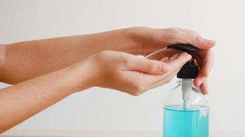 aziatische vrouw die alcoholgel handdesinfecterend middel gebruikt om de hand te wassen om het coronavirus te beschermen. vrouw duwt alcoholfles om hand schoon te maken voor hygiëne wanneer sociale afstand thuis blijft en zelfquarantainetijd. foto