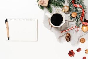 minimale creatieve platte lay van winterkerst traditionele compositie en nieuwjaarsvakantieseizoen. bovenaanzicht open mockup zwarte notebook voor tekst op witte achtergrond. bespotten en kopiëren van ruimtefotografie. foto