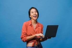 verraste jonge Aziatische dame met behulp van laptop met positieve uitdrukking, breed glimlachen, gekleed in casual kleding en camera kijken op blauwe achtergrond. gelukkige schattige blije vrouw verheugt zich over succes. foto