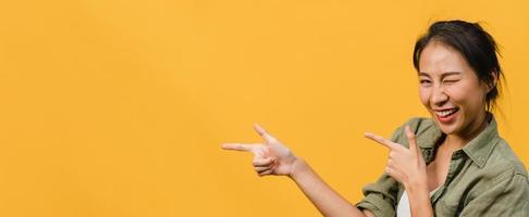 jonge aziatische dame lacht met vrolijke uitdrukking, toont iets geweldigs op lege ruimte in casual doek en kijkt naar camera geïsoleerd over gele achtergrond. panoramische banner met kopie ruimte. foto