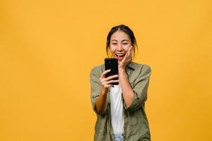 verraste jonge aziatische dame met behulp van mobiele telefoon met positieve uitdrukking, glimlacht breed, gekleed in casual kleding en staat geïsoleerd op gele achtergrond. gelukkige schattige blije vrouw verheugt zich over succes. foto