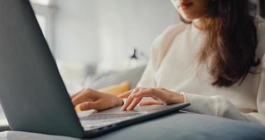close-up freelance azië dame vrijetijdskleding met behulp van laptop online leren in de woonkamer thuis. thuiswerken, op afstand, onderwijs op afstand, social distancing, quarantaine voor coronaviruspreventie. foto