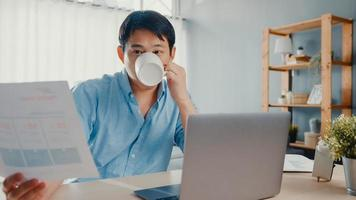 freelance aziatische man vrijetijdskleding met behulp van laptop en koffie drinken in de woonkamer thuis. thuiswerken, werken op afstand, onderwijs op afstand, social distancing, quarantaine voor preventie van het coronavirus. foto
