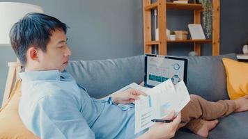freelance aziatische man vrijetijdskleding met behulp van laptop online leren in de woonkamer thuis. thuiswerken, werken op afstand, onderwijs op afstand, social distancing, quarantaine voor preventie van het coronavirus. foto