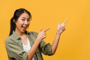 portret van een jonge aziatische dame die lacht met een vrolijke uitdrukking, laat iets geweldigs zien op lege ruimte in casual doek en kijkt naar camera geïsoleerd over gele achtergrond. gezichtsuitdrukking concept. foto