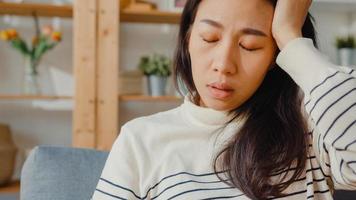 nadenkende aziatische dame zit knieën te omhelzen op de bank in de woonkamer in huis kijk naar buiten met eenzaam voelen, verdrietig depressieve tiener tijd alleen doorbrengen thuis blijven, sociale afstand, coronavirus quarantaine. foto
