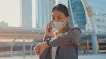 jonge Aziatische zakenvrouw in mode-kantoorkleding draagt een medisch gezichtsmasker, praat via de telefoon terwijl ze alleen buiten in de stedelijke stad loopt. zaken onderweg, sociale afstand om verspreiding van het covid-19-concept te voorkomen. foto