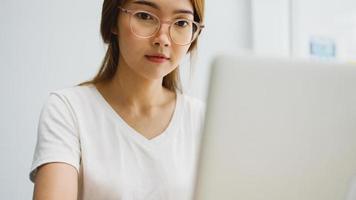 freelance jonge azië zakenvrouw vrijetijdskleding met behulp van laptop werken in de woonkamer thuis. thuiswerken, werken op afstand, zelfisolatie, sociale afstand, quarantaine voor preventie van het coronavirus. foto