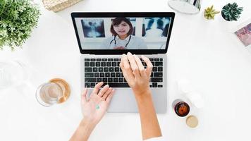 bovenaanzicht van jonge dame die computerlaptop gebruikt, praat over een ziekte in een videoconferentiegesprek met azië arts online consultatie in de woonkamer thuis. sociale afstand, quarantaine voor coronavirus. foto
