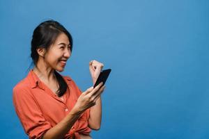 verraste jonge aziatische dame met behulp van mobiele telefoon met positieve uitdrukking, glimlacht breed, gekleed in casual kleding en staat geïsoleerd op blauwe achtergrond. gelukkige schattige blije vrouw verheugt zich over succes. foto