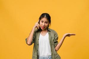 jonge aziatische dame praat via de telefoon met negatieve uitdrukking, opgewonden geschreeuw, huil emotioneel boos in casual doek en staat geïsoleerd op gele achtergrond met lege kopie ruimte. gezichtsuitdrukking concept. foto