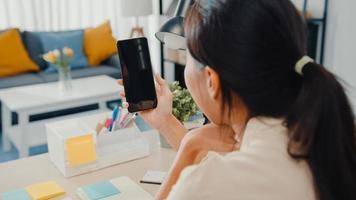 jonge aziatische dame gebruikt een smartphone met een leeg zwart scherm mock-up display voor reclametekst terwijl ze slim vanuit huis in de woonkamer werkt. chroma key-technologie, marketing ontwerpconcept. foto