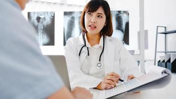jonge azië vrouwelijke arts in wit medisch uniform met klembord levert geweldig nieuws praten resultaten of symptomen bespreken met mannelijke patiënt zittend aan een bureau in een gezondheidskliniek of ziekenhuiskantoor. foto