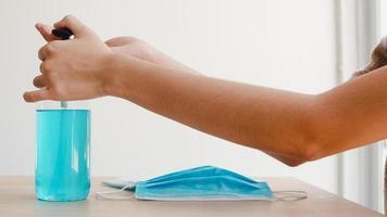aziatische vrouw die alcoholgel handdesinfecterend middel gebruikt, was de hand voordat ze een masker draagt om het coronavirus te beschermen. vrouw duwt alcohol om schoon te maken voor hygiëne wanneer sociale afstand thuis blijft en zelfquarantainetijd. foto
