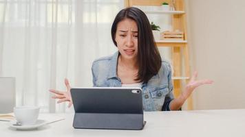 gefrustreerde jonge aziatische dame die problemen heeft met een niet werkende tabletcomputer die op een bureau zit. freelance slimme zakelijke vrouwen vrijetijdskleding met behulp van tablet werken op de werkplek in de woonkamer op kantoor aan huis. foto