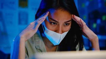 freelance azië vrouwen dragen gezichtsmasker met behulp van laptop hard werken op nieuw normaal kantoor. 's nachts thuiswerken, zelfisolatie, sociale afstand, quarantaine voor preventie van het coronavirus. foto