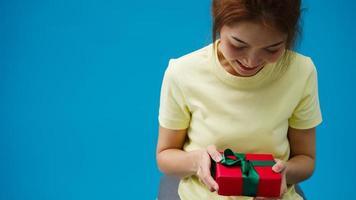 jonge Azië meisje glimlach en ontvangen huidige doos geïsoleerd op blauwe achtergrond. kopieer ruimte voor het plaatsen van een tekst, bericht voor reclame. advertentiegebied, mockup promotionele inhoud. foto