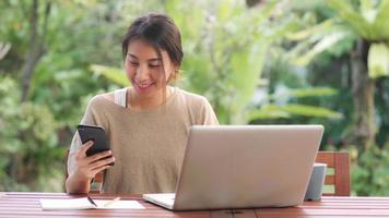 freelance aziatische vrouw die thuis werkt, zakelijke vrouw die op laptop werkt en mobiele telefoon gebruikt die koffie drinkt zittend op tafel in de tuin in de ochtend. levensstijl vrouwen die thuis werken concept. foto