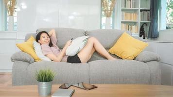 jonge aziatische tienervrouw die thuis tv kijkt, vrouw voelt zich gelukkig liggend op de bank in de woonkamer. levensstijl vrouw ontspannen in de ochtend thuis concept. foto