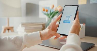 jonge aziatische dame gebruikt mobiel om online winkelproduct te bestellen en rekeningen te betalen met bank-app met succesvolle transactie. thuis blijven, quarantaine-activiteit, leuke activiteit voor coronaviruspreventie. foto