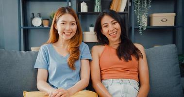 tiener paar aziatische vrouwen voelen zich gelukkig lachend en kijken naar de camera terwijl ze ontspannen in de woonkamer thuis. vrolijke kamergenoot dames videogesprek met vriend en familie, lifestyle vrouw thuis concept. foto