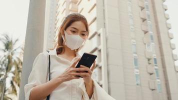 succesvolle jonge Aziatische zakenvrouw in mode-kantoorkleding met een medisch gezichtsmasker met behulp van een smartphone terwijl ze 's ochtends alleen buiten in de stedelijke moderne stad loopt. bedrijf onderweg concept. foto