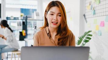 azië zakenvrouw sociale afstand in nieuwe normale situatie voor viruspreventie tijdens het gebruik van laptoppresentatie aan collega's over plan in videogesprek terwijl u op kantoor werkt. leven na corona. foto