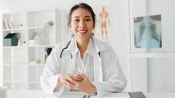 jonge azië dame arts in wit medisch uniform met stethoscoop met behulp van computer laptop praten videoconferentiegesprek met patiënt, kijkend naar camera in gezondheidsziekenhuis. advies- en therapieconcept. foto