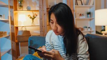 nadenkende aziatische dame die telefoon vasthoudt verdrietig wachtend op oproep zit op de bank in de woonkamer thuis 's nachts voel me eenzaam, verdrietig depressieve tiener brengt tijd alleen door, sociale afstand, coronavirus quarantaine. foto