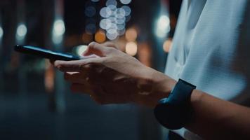 jonge azië zakenvrouw in mode kantoorkleding met behulp van smartphone sms-bericht te typen terwijl ze 's nachts buiten in de stedelijke moderne stad staat. bedrijf onderweg concept. Close-up shot. foto