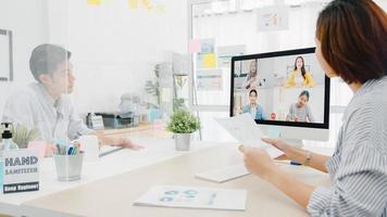 Aziatische zakenmensen die desktop gebruiken, praten met collega's die zakelijke brainstorm over plan bespreken in een videogesprekvergadering in een nieuw normaal kantoor. levensstijl sociale afstand en werk na het coronavirus. foto