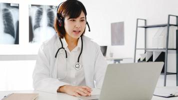 jonge Aziatische vrouwelijke arts in wit medisch uniform met stethoscoop met behulp van computerlaptop praten videoconferentiegesprek met patiënt aan balie in gezondheidskliniek of ziekenhuis. advies- en therapieconcept foto