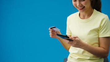 jonge aziatische dame met behulp van telefoon en creditcard met positieve uitdrukking, glimlacht breed, gekleed in casual kleding en staat geïsoleerd op blauwe achtergrond. gelukkige schattige blije vrouw verheugt zich over succes. foto