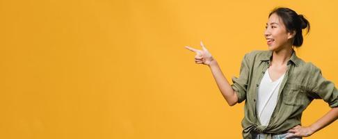 portret van een jonge aziatische dame die lacht met een vrolijke uitdrukking, toont iets geweldigs op lege ruimte in casual kleding en staat geïsoleerd op een gele achtergrond. panoramische banner met kopie ruimte. foto