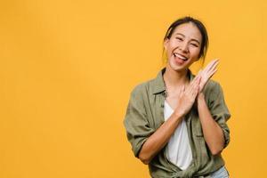 jonge azië dame met positieve uitdrukking, breed glimlachen, gekleed in casual kleding en camera kijken over gele achtergrond. gelukkige schattige blije vrouw verheugt zich over succes. gezichtsuitdrukking concept. foto