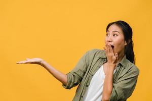 portret van een jonge aziatische dame die lacht met een vrolijke uitdrukking, toont iets geweldigs op lege ruimte in casual kleding en staat geïsoleerd op een gele achtergrond. gezichtsuitdrukking concept. foto