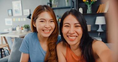tiener aziatische vrouwen voelen zich gelukkig lachend selfie en kijken naar de camera terwijl ze ontspannen in de woonkamer thuis. vrolijke kamergenoot dames videogesprek met vriend en familie, lifestyle vrouw thuis concept. foto