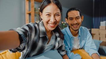 gelukkige jonge Aziatische paar man en vrouw zitten op de bank te kijken naar camera videogesprek met vrienden en familie in de woonkamer thuis. blijf thuis quarantaine, sociale afstand, jong getrouwd concept. foto