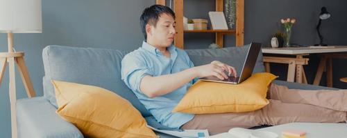 freelance aziatische man vrijetijdskleding met behulp van laptop online leren in de woonkamer thuis. thuiswerken, werken op afstand, onderwijs op afstand, sociale afstand, panoramische bannerachtergrond met kopieerruimte. foto