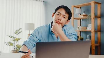 freelance azië man vrijetijdskleding met behulp van laptop online in de woonkamer op kantoor aan huis. thuiswerken, werken op afstand, onderwijs op afstand, social distancing, quarantaine voor preventie van het coronavirus. foto