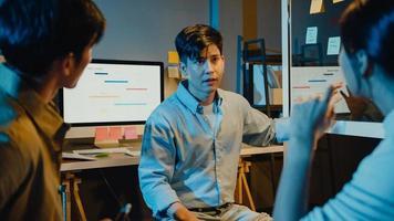 Azië zakenmensen staan achter transparante glazen wand luisteren manager wijst voortgangswerk en brainstormvergadering en werknemer post plakkerige nota in kantoor nacht. zakelijke inspiratie, ideeën delen. foto