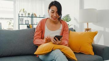 mooie dame met behulp van smartphone chat met paar zittend op de bank in de woonkamer thuis in de ochtend. blijf thuis, quarantaine voor covid, nomofobie, online winkelen, sociaal netwerkverslavingsconcept. foto