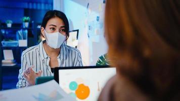Azië zakenmensen met behulp van laptop presentatie en communicatie vergadering brainstormen ideeën over nieuwe project collega's werken plan succes strategie dragen gezichtsmasker terug in nieuw normaal nachtkantoor. foto