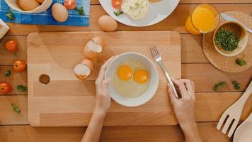 handen van jonge aziatische vrouw chef-kok die ei in keramische kom zwaait, kook omelet met groenten op een houten bord op de keukentafel in huis. levensstijl gezond eten en traditionele bakkerij. bovenaanzicht schot. foto