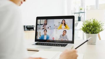 azië zakenvrouw met behulp van laptop praten met collega's over plan in videogesprek vergadering tijdens het werken vanuit huis in de woonkamer. zelfisolatie, sociale afstand, quarantaine voor preventie van het coronavirus. foto