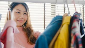 mooie aantrekkelijke jonge aziatische dame die haar mode-outfit kleding in de kast in huis of winkel kiest. meisje denk wat te casual shirt te dragen. thuis garderobe of kledingwinkel kleedkamer. foto