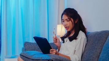 Aziatische zakenvrouw die tablet gebruikt, praat met collega's over het plan in een videogesprek terwijl ze 's nachts vanuit huis in de woonkamer werkt. zelfisolatie, sociale afstand, quarantaine voor coronaviruspreventie. foto