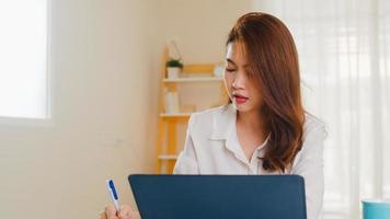 portret van freelance azië vrouwen vrijetijdskleding met behulp van laptop die in de woonkamer thuis werkt. thuiswerken, werken op afstand, zelfisolatie, sociale afstand, quarantaine voor coronaviruspreventie. foto